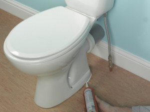 applying silicone sealant around the base of the toilet pan