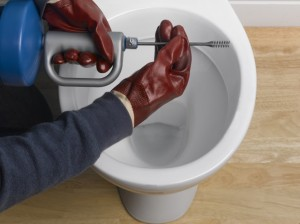 Using an auger to unblock toilet