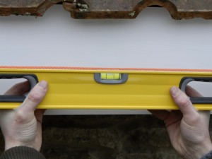 hold spirit level against taut string line