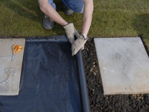 rolling out weedproof membrane