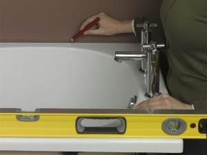 Drawing pencil guideline on wall to position bath