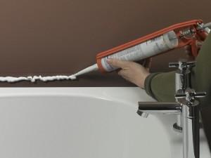 Applying silicone sealant to position bath