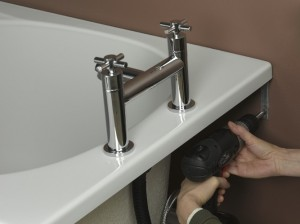 Screwing bracket in to hold bath in place