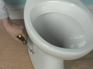 screwing toilet pan in place