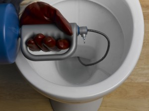 Pushing auger into toilet U-bend