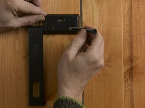 inserting bolts or screws to secure the hasp plate