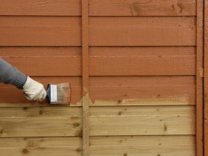 painting fence with brush