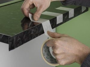 Sticking down using masking tape to allow adhesive to go off